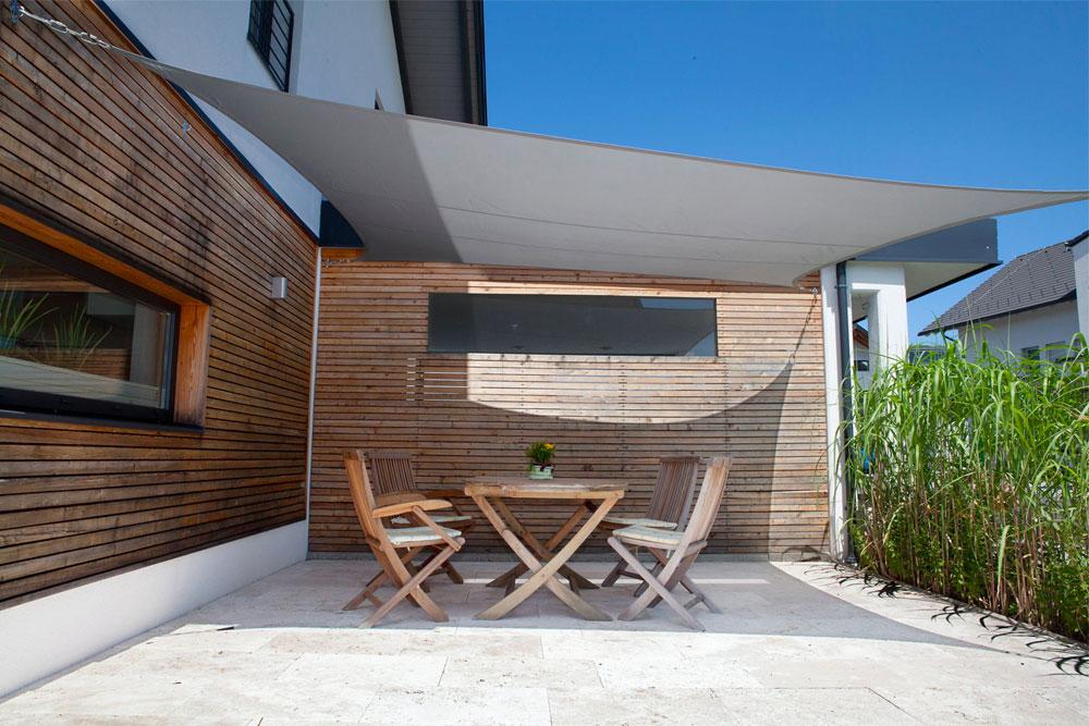 Toldo vela rectangular sujetada sobre la fachada de la vivienda
